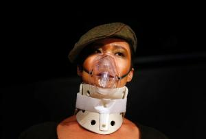 A model wearing an oxygen mask, walks along a make-shift catwalk during a fashion show organized by environmental group Greenpeace titled 'Toxic Threads - The Big Fashion Stitch-Up', in Beijing November 20, 2012. (photo courtesy of REUTERS/David Gray)