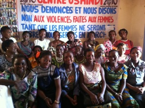 "The women of Mamafrica, in front of a sign that reads ""We Denounce and We Say NO to Violence Against Women!"""